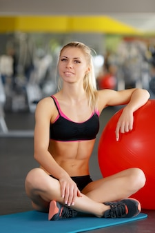 Vrouw zittend op de vloer van een sportschool