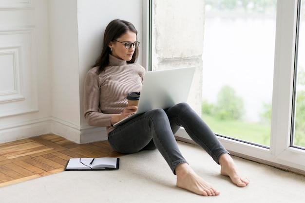 Vrouw zittend op de vloer werken op haar laptop