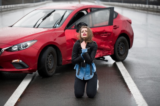 Vrouw zittend op de weg na een ongeval. gewonde vrouw die zich slecht voelt na een auto-ongeluk