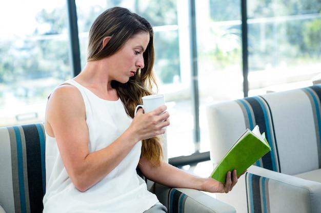 Vrouw, zittend op een bank, een boek lezen en een kopje koffie drinken