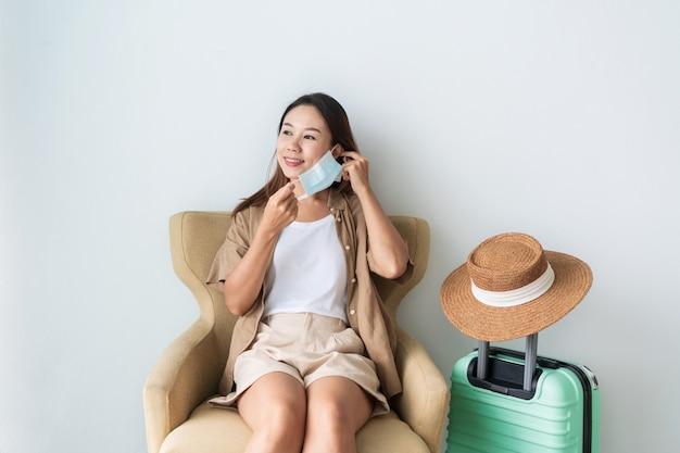 Vrouw zittend op een bank tijdens het opstijgen van medische masker