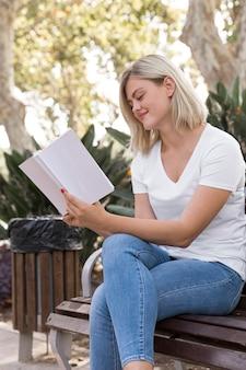 Vrouw zittend op een bankje buiten en boek lezen