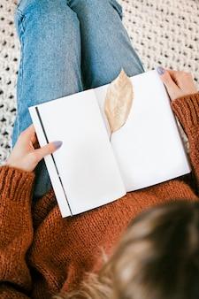 Vrouw zittend op een gebreid tapijt met een gouden knapperig blad op een open notebook