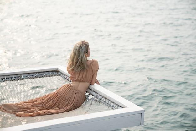 Vrouw zittend op een pier met zee achtergrond, zitten op het net aan zee.