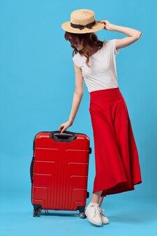 Vrouw zittend op een rode koffer reizen levensstijl vlucht blauwe achtergrond