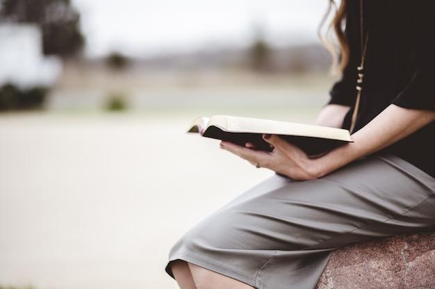 Vrouw zittend op een rots buiten tijdens het lezen van een boek