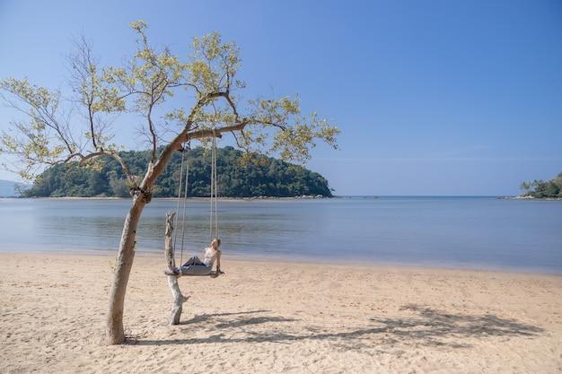 Vrouw zittend op een schommel, op het strand.