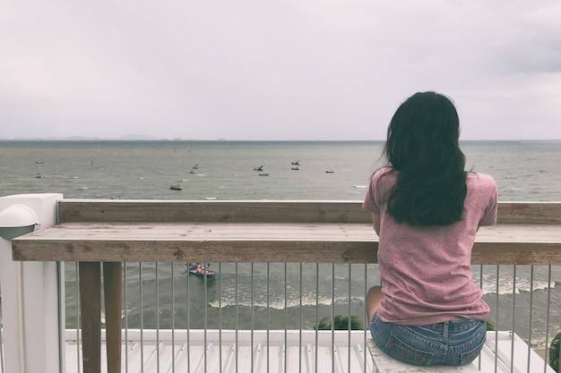 Vrouw zittend op een stoel en kijken naar de zee