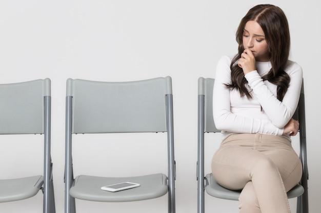 Vrouw zittend op een stoel en kijken naar smartphone, wachtend op het telefoontje of sms-bericht