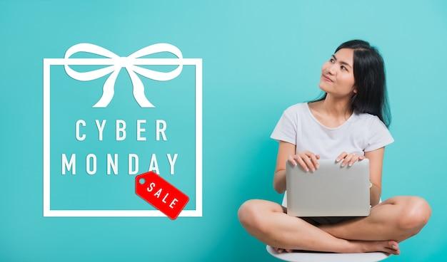 Vrouw zittend op een stoel en laptop met cyber monday-tekst te houden