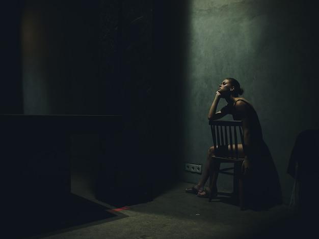 Vrouw zittend op een stoel in een donkere kamer vallende licht eenzaamheid emoties overstuur depressie