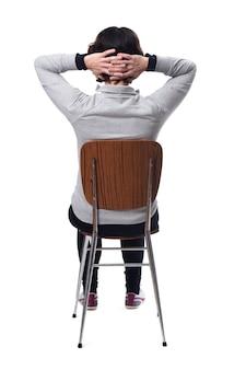 Vrouw zittend op een stoel met haar rug op een witte achtergrond