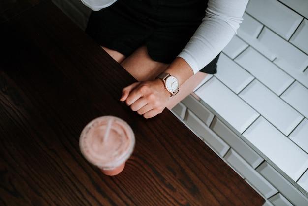 Vrouw zittend op een witte decoratieve bakstenen bankje met een aardbei milkshake naast haar