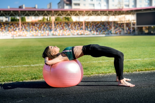Vrouw zittend op fitball. jonge en sportieve vrouw die buitenshuis traint