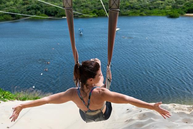 Vrouw zittend op haar rug en zijwaarts kijkend op een zip-line met uitzicht op de jacoma-lagune.
