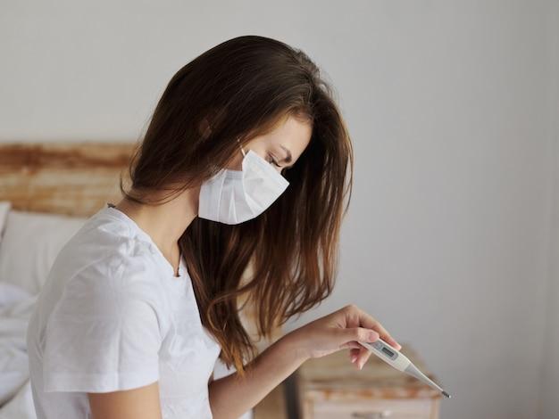 Vrouw zittend op het bed in de slaapkamer zonder thermometer in haar handen