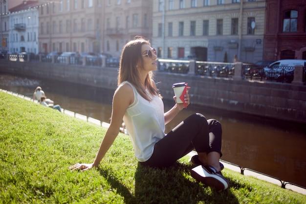 Vrouw zittend op het gras koffie drinken in een kartonnen beker