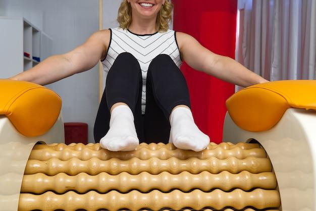 Vrouw zittend op het massagegereedschap voor de benen met een grote vreugde op haar gezicht