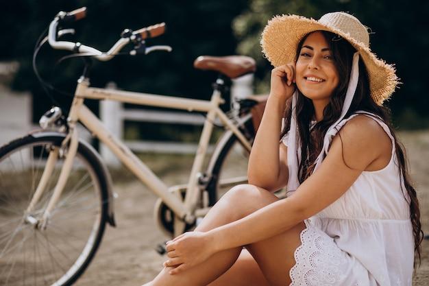 Vrouw zittend op het strand bij de fiets