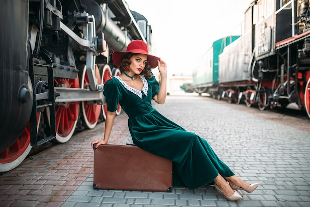 Vrouw zittend op koffer tegen stoomtrein