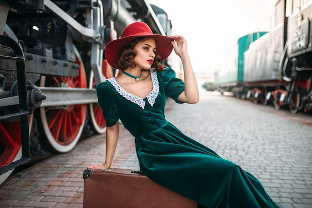 Vrouw zittend op koffer tegen stoomtrein Premium Foto