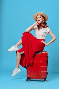 Vrouw zittend op rode koffer emoties charme levensstijl reizen. hoge kwaliteit foto