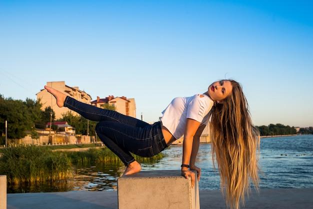 Vrouw zittend op steen aan de oever van het meer