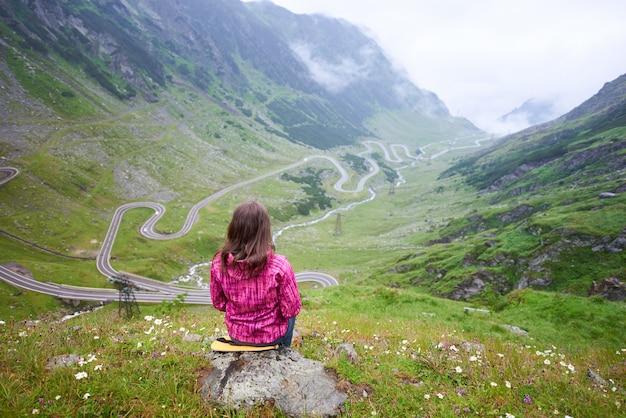 Vrouw zittend op steen en een spectaculair uitzicht op groene rotsen bewonderen