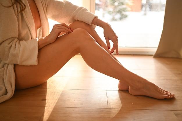Vrouw zittend op warme houten vloer thuis zonnige dag.