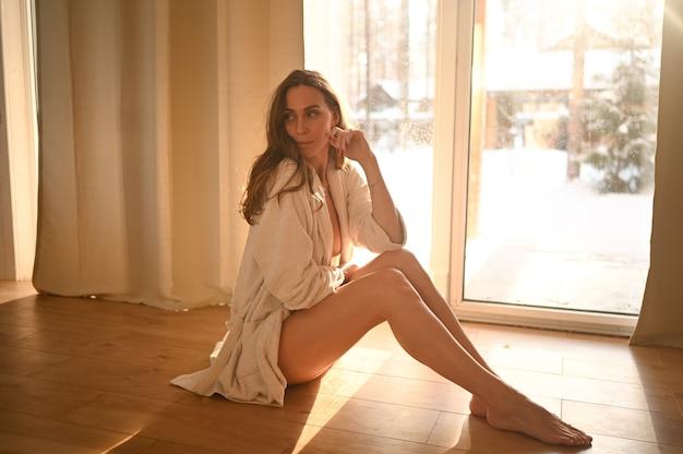 Vrouw zittend op warme vloer thuis zonnige dag