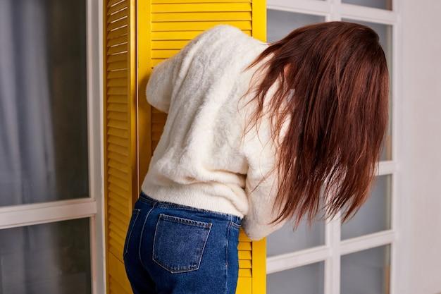 Vrouw zoekt kleding in kleedkamer vrouw laat zien dat ze een blauwe spijkerbroek draagt