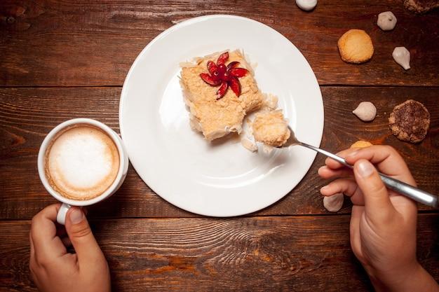 Vrouw zoete dessert kopje koffie eten op houten tafel
