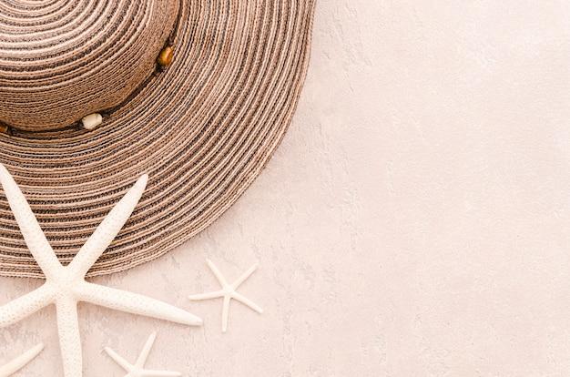 Vrouw zomer hoed met zeesterren op tafel