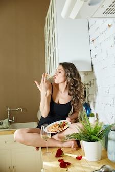 Vrouw zonder complexen eet thuis pizza en spaghetti. vreugde en gelach op het gezicht van de vrouw