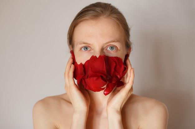 Vrouw zonder cosmetica die een masker van rozenblaadjes draagt, ziet er recht uit