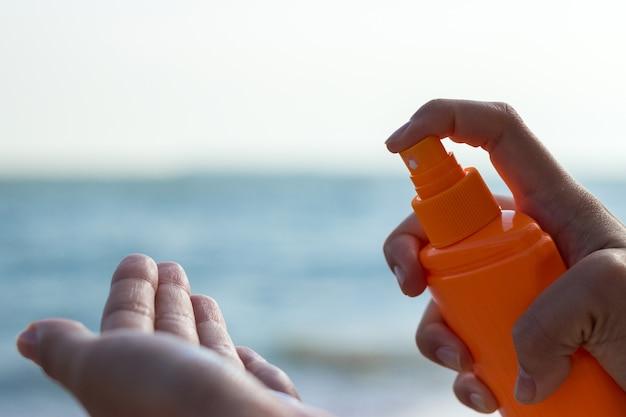 Vrouw zonnebrandcrème in een hand gieten
