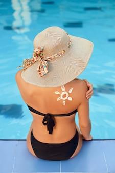 Vrouw zonnebrandcrème op schouder buiten zetten bij zwembad onder zon op mooie zomerdag.