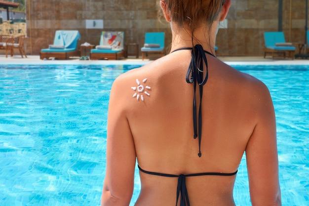 Vrouw zonnebrandcrème toe te passen op gebruinde schouder. huidsverzorging. zon bescherming. meisje met behulp van zonnebrandcrème op rug