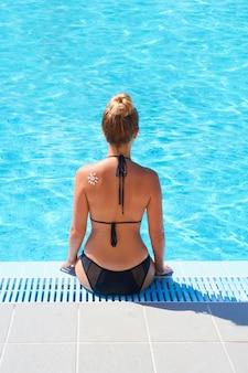 Vrouw zonnebrandcrème toe te passen op gebruinde schouder in vorm van de zon. bescherming tegen de zon. zonnebrandcrème. huid- en lichaamsverzorging. meisje met behulp van zonnebrandcrème op de huid.