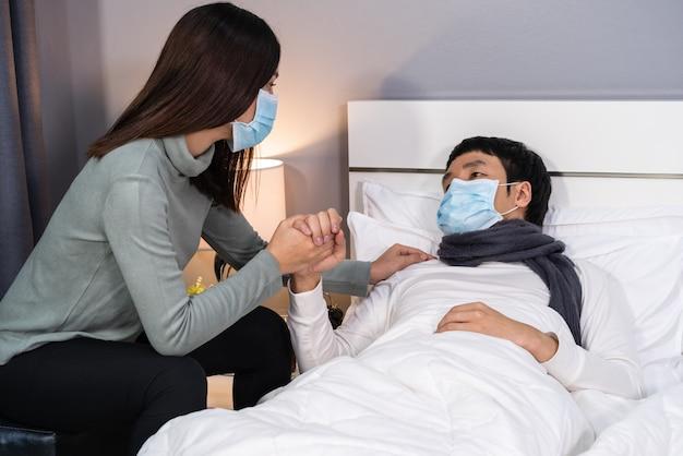 Vrouw zorgt thuis voor haar zieke man op bed, mensen moeten een medisch masker dragen dat beschermt tegen een pandemie van het coronavirus