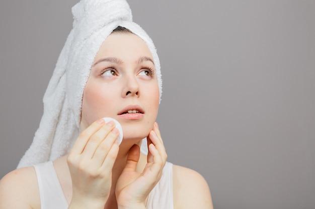 Vrouw zorgt voor haar gezicht, na een douche in een handdoek op een grijs, een wattenschijfje in haar hand