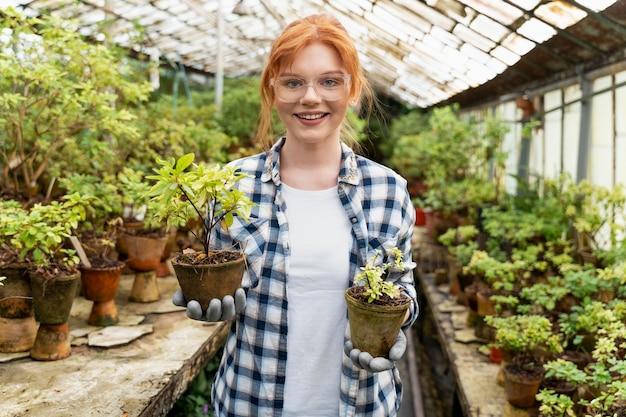 Vrouw zorgt voor haar planten in een kas