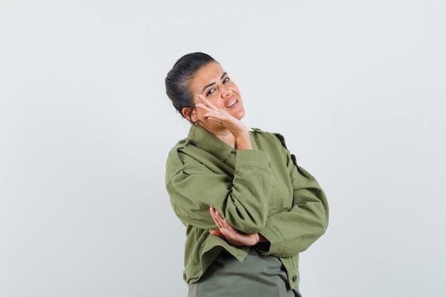 Vrouw zwaaien hand in jas, t-shirt en op zoek zelfverzekerd