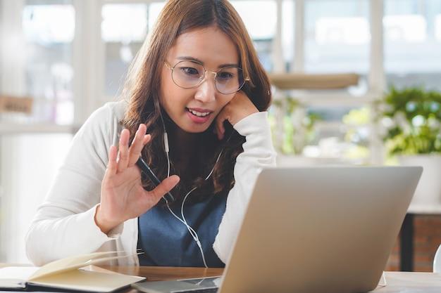 Vrouw zwaaiende handen groet collega's in videoconferentievergadering