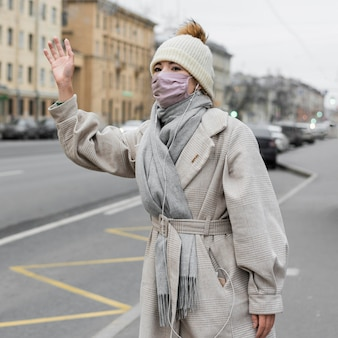 Vrouw zwaait in de stad terwijl ze een medisch masker draagt