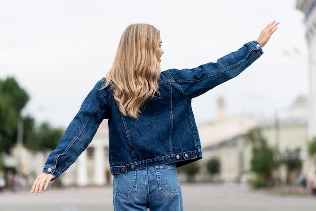 Vrouw zwaait met haar handen vanaf de achterkant schot