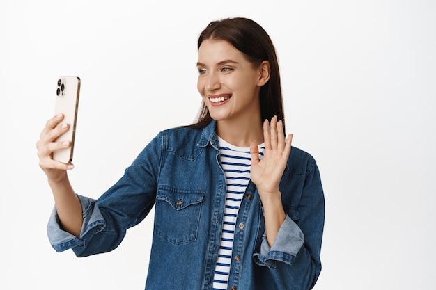 Vrouw zwaait naar vriend tijdens videogesprek, glimlacht en kijkt naar smartphonecamera, voert een gesprek via mobiele app, zegt hallo, neemt blog op, livestream met applicatie op wit