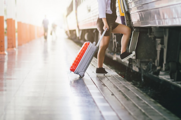 Vrouw zwangere reizigers nemen een trein met het dragen van haar trolley rode tas op het station reizen.