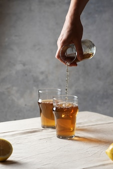 Vrouw zwarte hete thee gieten in een glas, beeld van de selectieve aandacht in minimalistische stijl