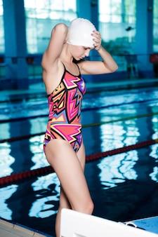 Vrouw zwemmer in een badmuts jurken glazen en klaar om te zwemmen